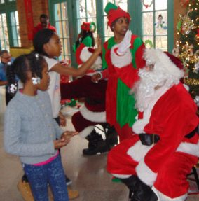 High fives all around for children visiting Santa at Loretto's 24th annual Christmas toy giveaway Dec. 13, at Columbus Park Refectory.