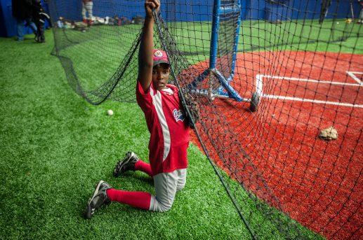 Jordan Fender 12, of the little league team of Garfield Park, goes under a net at UIC's Curtis Granderson Stadium (William Camargo/Contributor)
