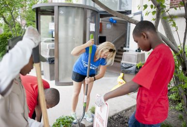 Project coordinator Polly Mulhearn helps volunteers plant flowers during cleanup efforts of Austin Plaza Arms, 501 N. Central Ave, held last Sat., May 16. (William Camargo/Staff Photographer)