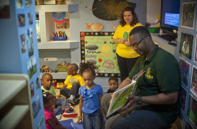 Levell Baker, of Vision Builders Early Childcare Learning Center, reads with children. William Camargo/Staff.