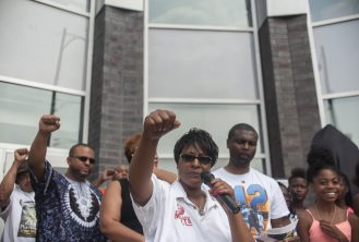 """STATUE UNVEILING: Alderman Emma Mitts of the 37th Ward, throws up her fist with the """"Black Power"""" gesture during a celebration for the naming of Mandela Road in the west side of Chicago on July 18, 2015. 