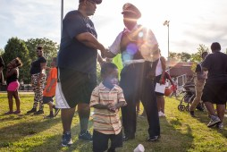 The son of Sharese Smith, Denim Smith, 8, walks past 15th District Commander Duane Betts at Moore Park, where National Night Out took place on Tue. August 4, 2015. | Alex Wroblewski/Contributor.