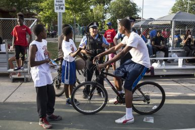 An officer speaks with community youths during the 15th District's National Night Out in Moore Park Tue. August 4. | Alex Wroblewski/Contributor