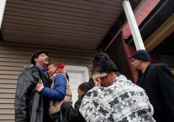 During a Dec. 27 prayer vigil, LaTonya Jones, 19, right, hugs her father Garry Mullins, 58, on the porch of the apartment building where her mother, Bettie Jones, was shot to death by Chicago police on Saturday, Dec. 26. | William Camargo/Staff.