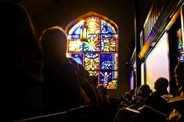 Congregants worshiping during a Jan. 17 service at First Church of the Brethren, where Martin Luther King, Jr., had an office during his fight against unjust housing in 1966. The stained glass window was installed in 2000, according to a congregant. | Sebastian Hidalgo/Contributor.