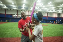 Coach Frank Brim, Garfield Park Little League's executive director, helps a player with her batting technique during an April 15 practice at Curtis Granderson Stadium on the Near West Side. | William Camargo/Staff