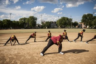 Coach J leads his team in some pregame stretches before the opening game of the North Lawndale Police Youth Baseball League, which will allow young players to see that cops are human, too, police say. | William Camargo/Staff