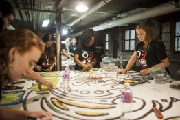 Oak Park and Austin students with Off the Wall, a summer arts apprenticeship program sponsored by the Oak Park Area Arts Council, put the finishing touches on murals inside the basement of an Austin apartment building on July 21. | William Camargo/Staff