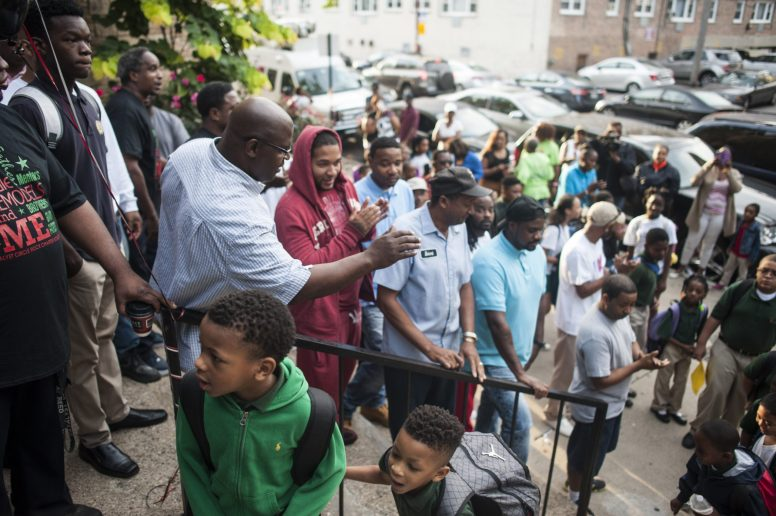 More than 200 fathers converge on the steps of Catalyst Circle Rock Charter School in Austin on Sept. 15 for the school's annual Dads Take Your Child to School initiative. | William Camargo/Staff