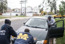 Two men push a stalled vehicle in the West Garfield Park neighborhood to auto body mechanic Glen Gray, far right, a Jamaican immigrant who is among many community residents who expressed shock and disappointment at the election of Donald J. Trump to the presidency. | William Camargo/Staff