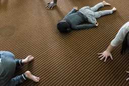 """A child sleeps face down during A House in Austin's yoga class, Saturday, Feb. 4, 2017, while other assemble a """"Downward Dog"""" yoga position at Austin Branch Chicago Public Library."""