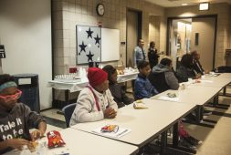 Family and winners sit and enjoy a small lunch as winners of the Black History Month Essay contest wait to be announced at the 15th District Police Headquarter on March 23, 2017.
