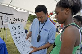 Charlie Smith III, left, of Chicago, gives an eye exam to Destynee Dixon, 19, of Chicago, on Saturday, Aug. 26, during Ald. Jason Ervin's Summer Festival at Marshall High School Campus Park in Chicago's Austin neighborhood. | ALEXA ROGALS/Staff Photographer