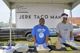 Len Griffin, left, of Chicago, and Jerk Man Taco manager Kenneth Murphy, of Chicago, hand out free tacos, during Ald. Jason Ervin's Summer Festival at Marshall High School Campus Park in Chicago's Austin neighborhood. | ALEXA ROGALS/Staff Photographer