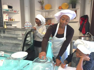 Neena and Isaiah help their mom, Chamille Weddington, set up their homemade Schweet cheesecake in the popup store.
