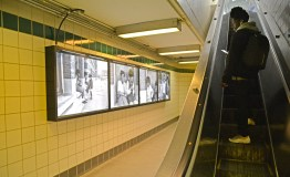 Just Looking: A customer walks to the exit and views Dorrell Creightney's photographs hung on the wall at the L Green Line Central Station on Central and Lake Street in Austin. | ALEXA ROGALS/Staff Photographer