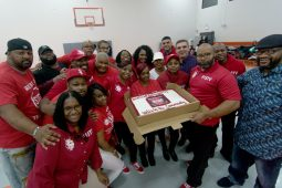 "Volunteers and members of Stop The Violence holding a custom made cake that reads, ""#1STV and Annual Drive, Unity in the Community."" 