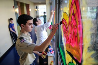 Value statement: James Kennedy, a junior at Oak Park and River Forest High School helps paint a mural at New Moms in Austin last Sunday, James also organized the event and brought his Boys Scout troop to help out. | WILLIAM CAMARGO/Contributor