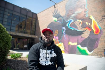 Chicago artist Max Sasing sits on May 7 near the mural he completed last week near the entrance of Michele Clark Magnet High School in Austin.
