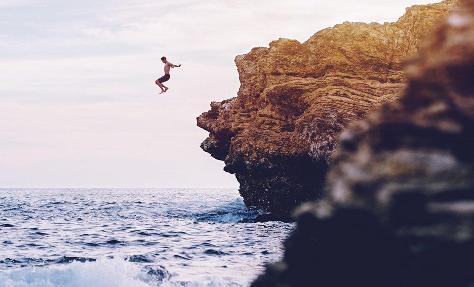 Image of someone jumping from a cliff - to represent why I believe it's important to try new thing when travelling solo