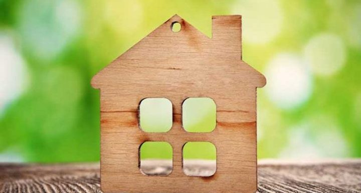 wooden home cutout on a green backdrop