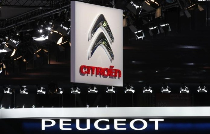 Peugeot and Citroen logos are seen over the French carmakers' showcases on media day at the Paris Mondial de l'Automobile