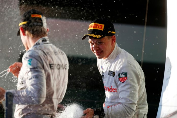 Kevin Magnussen sprays the champagne on the podium.