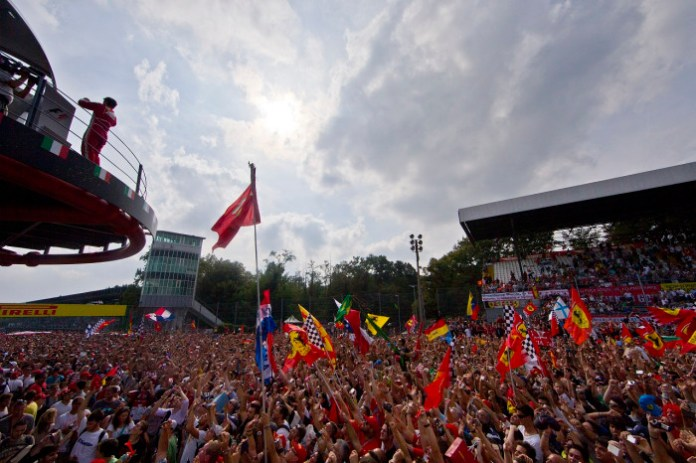 Autodromo Nazionale, Monza, Italy. 8th September 2013 Fans celebrate with flags on the track beneath the podium as Fernando Alonso takes a picture Photo: Lorenzo Bellanca/Ferrari. ref: _00P4305