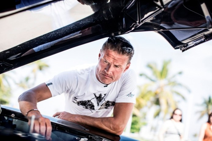 Former Formula 1 race car driver David Coulthard looks at the engine of a classic car in old Havana, Cuba on August 16, 2013.