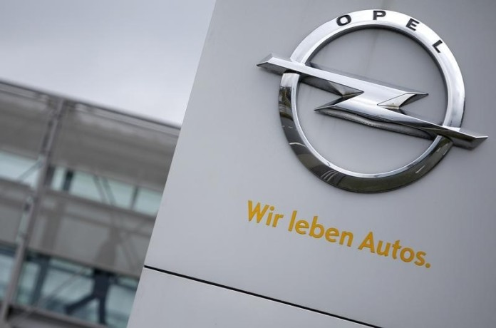 A sign depicting the Opel logo is pictured in front of the Opel Adam AG headquarters as a person passes by in Ruesselheim