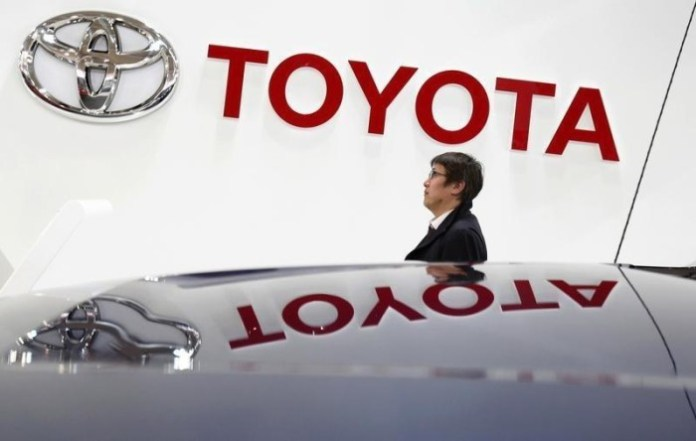 A visitor walks under a logo of Toyota Motor Corp at the company's showroom in Tokyo