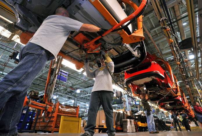 Workers at Ford's Michigan Assembly Plant attach a charger to a 100% battery Focus Electric, one of five vehicles built at the facility. ÔFlexible work stations make MAP the only manufacturing site in the world to build vehicles with five different fuel-efficient powertrains on the same line,Õ Ford says.