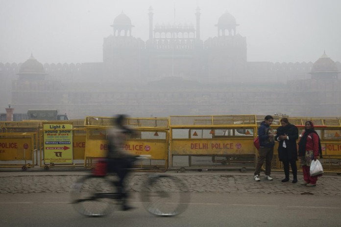 A cyclist passes police barricades in front of the Red Fort shrouded in haze in New Delhi, India, on Monday, Jan. 20, 2014. India, China and Brazil, three of the largest developing nations, joined the U.S. in a list of the biggest historical contributors to global warming, according to a study by researchers in Canada. Photographer: Kuni Takahashi/Bloomberg via Getty Images