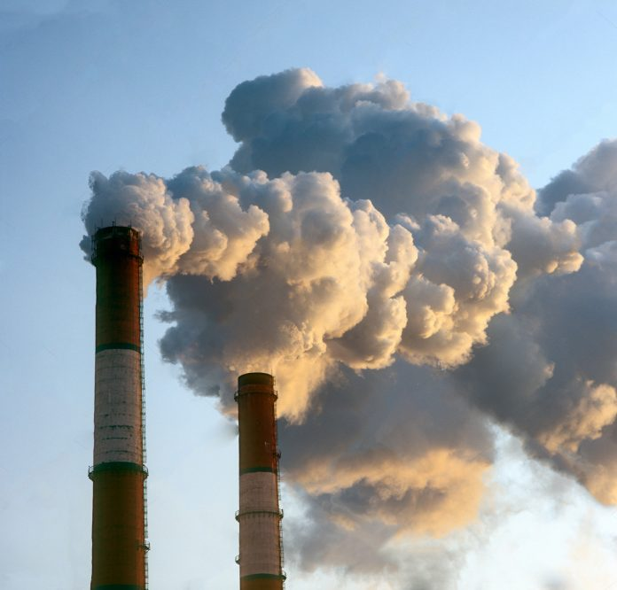stock-photo-air-pollution-by-smoke-coming-out-of-two-factory-chimneys-100872778