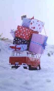 Miniatura de perua Kombi na neve com presentes gigantes amarados na capota, foto