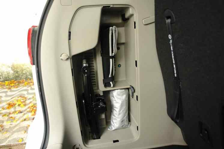 Macaco, chave de roda. A bolsa prateada é para guardar o pneu furado, evitando sujar o porta-malas