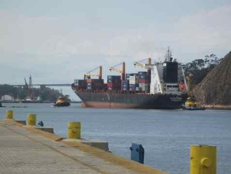 Rebocadores manobram navio para deixar Porto de Vitória. A 3ª ponte é visível ao fundo