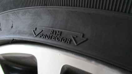 Pneu com aba de proteção para a roda