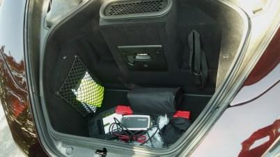 No porta-malas tem espaço para bolsas e sacolas. Veja o carregador da bateria. Ao lado da lâmpada tem a tomada 12 V para carregar o carro, ou para qualquer aparelho de 12 V