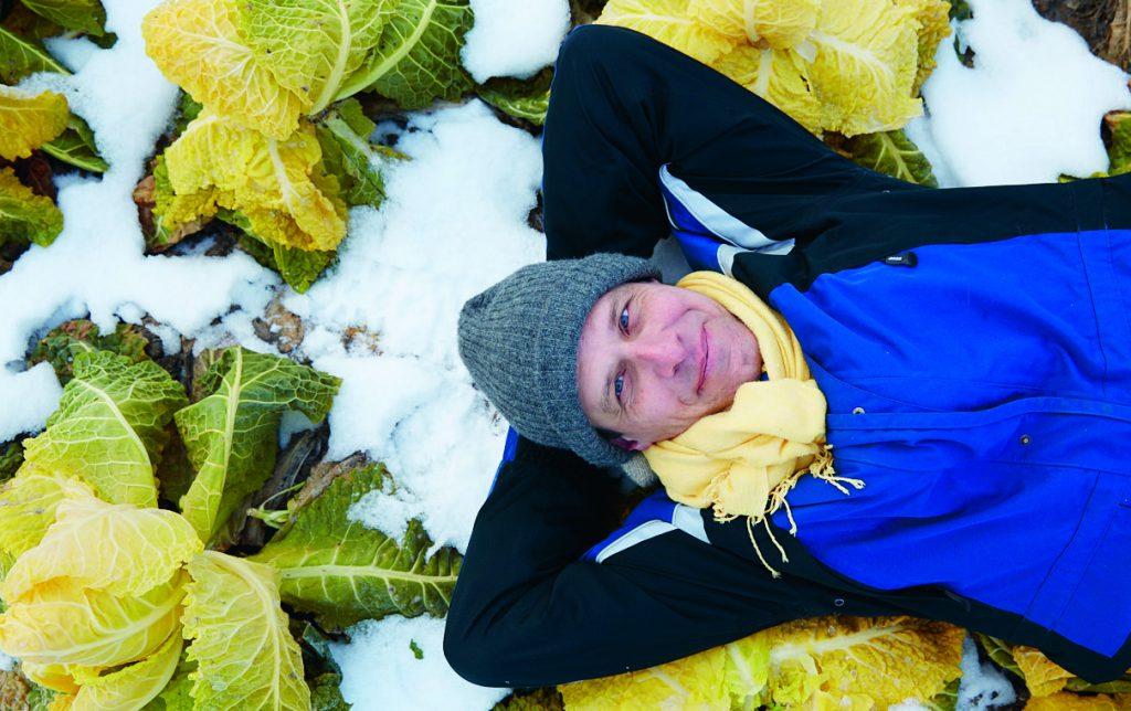 Forscher Wolfgang Palme liegt in einem Beet mit verschneitem Wintergemüse