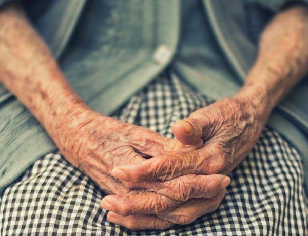 eine alte Bäuerin sitzt und faltet ihre alten Hände unter dem Bauch. Sie trägt ein Kariertes Kleid und denkt an Kunstdünger