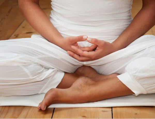 eine weiß gekleidete Frau in der Meditation