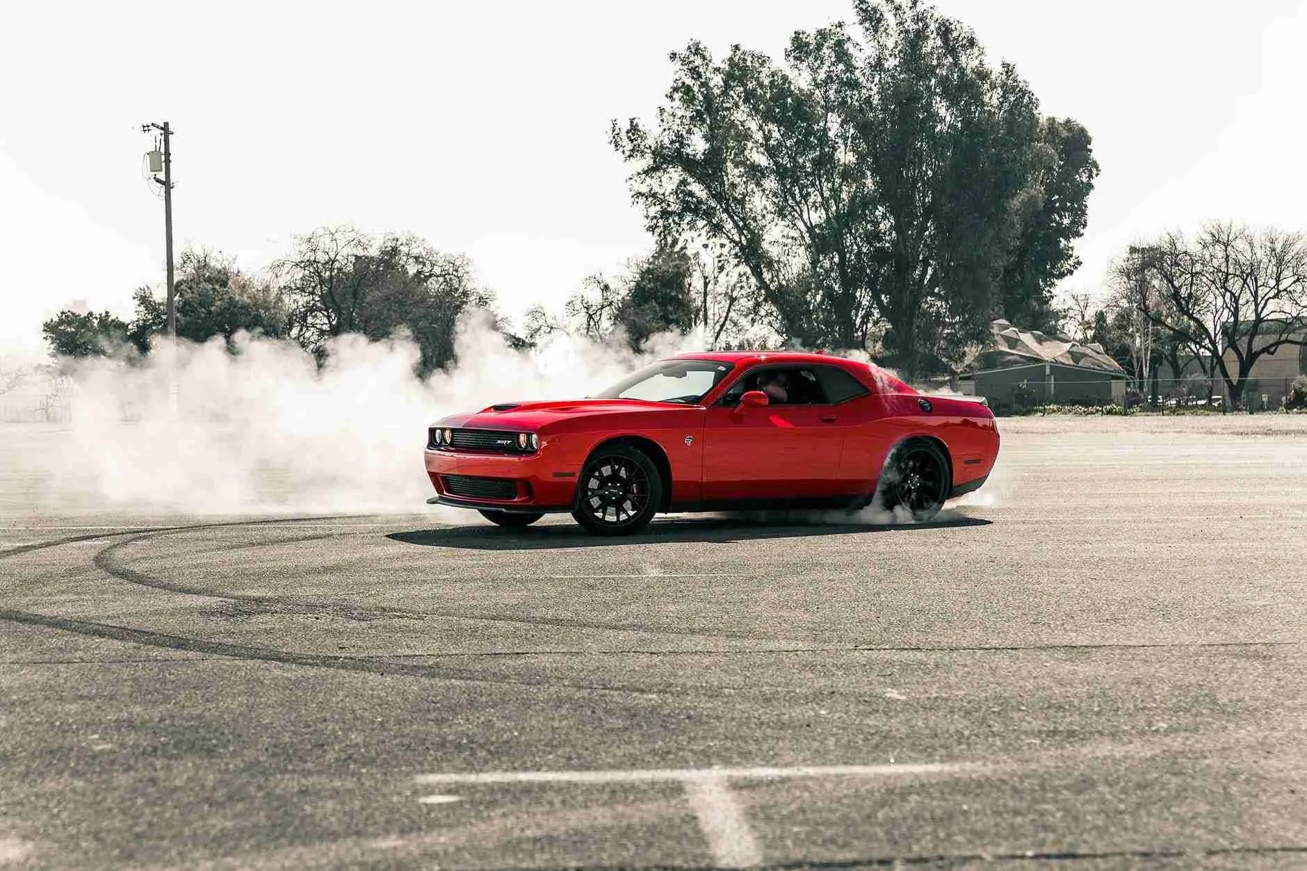 red coupe drifting on asphalt road