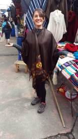 Laura essaie un poncho sur la place aux ponchos à Otavalo