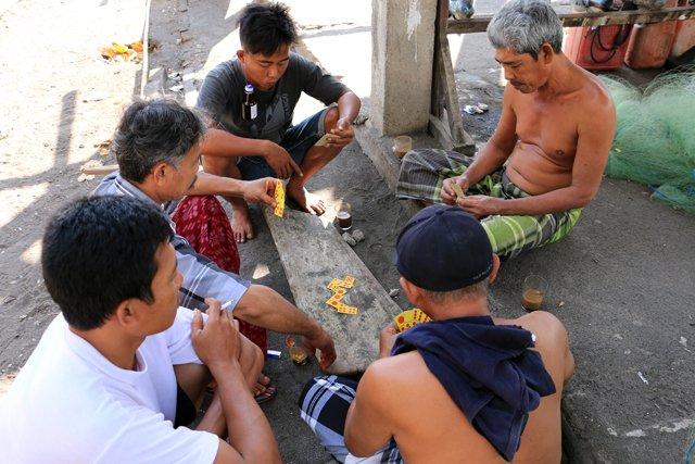 hommes jouant au dominos...si tu perds on te pends une bouteille à l'oreille