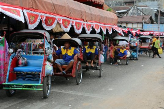 becaks attendant le client dans la rue principale de Malioboro