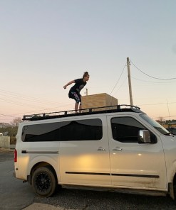Woman jumping on Nissan nv3500 roof rack from Avatar Metal Works with fairing.