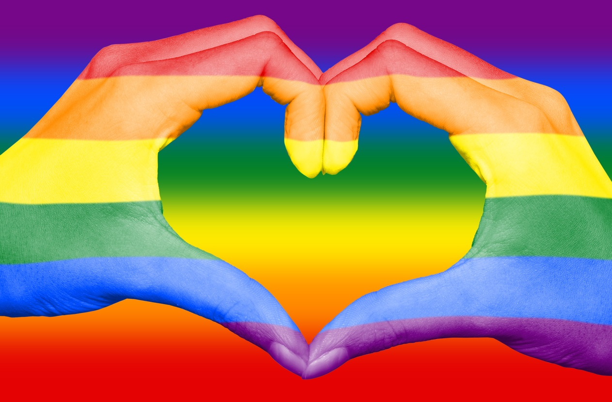 Gay rainbow flag painted on hands forming a heart on rainbow background, gay and LGBT love concept