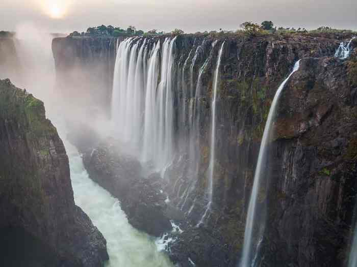 Long exposure of Victoria Falls sunset with zambezi river and red sun, View from Zambia