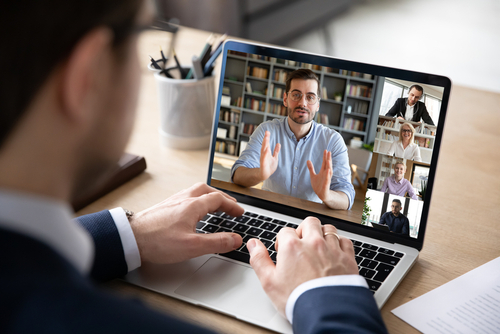 business professional sitting at his home desk partaking in virtual meeting